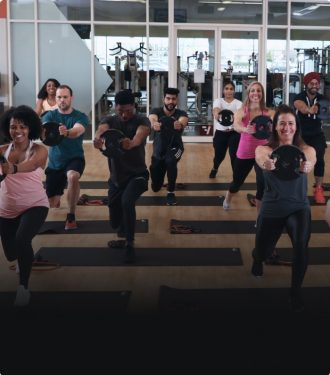 Group of people in a fitness class, each holding a light weight plate and lunging with their left foot forward