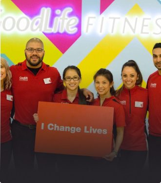 "Six GoodLife Fitness associates holding a sign that says ""I Change Lives"""