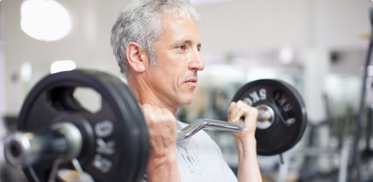 Man in grey shirt holds barbell to chest with arms bent