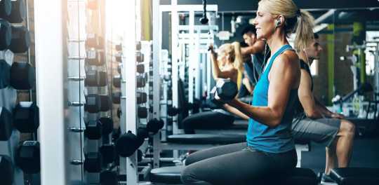 Woman with earbuds in blue tank top sitting on bench doing bicep curls with free weights