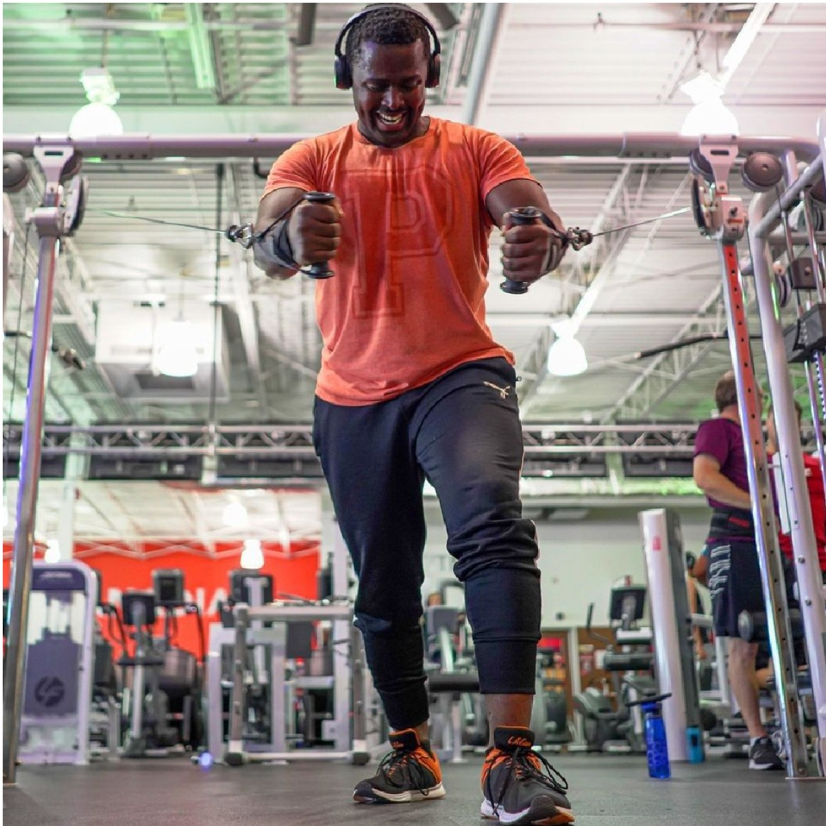 man in orange t-shirt with headphones does a chest press on a pulley machine