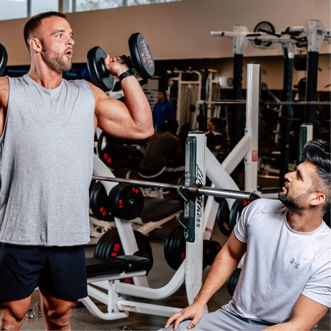 Man in grey shirt does standing shoulder presses with dumbbells while a second man on a bench in a white t-shirt observes his form