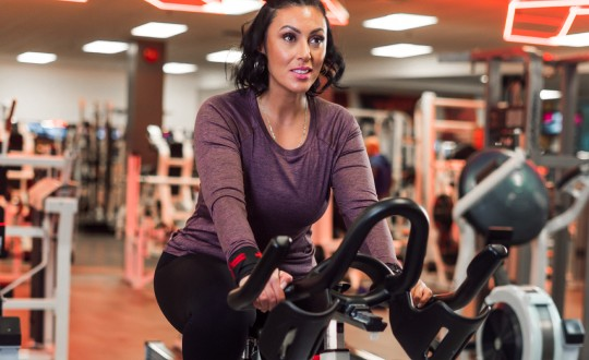 Woman in purple long-sleeved shirt trains on stationary bicycle