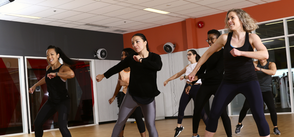 Seven people participating in a group fitness class