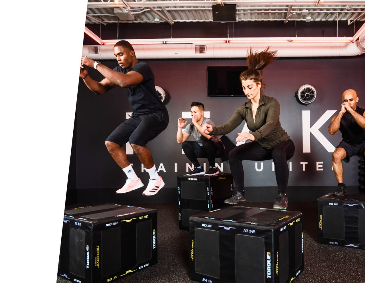 Four people doing box jumps onto black boxes in PEAK training space