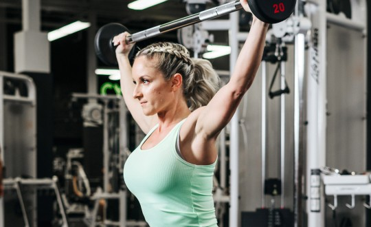 Woman in mint green tank top doing a barbell squat in weight area