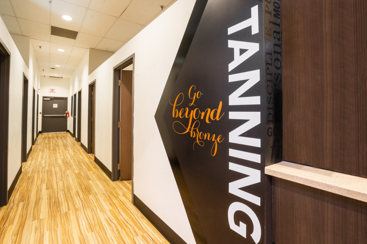"A long corridor of tanning rooms with open doors and a sign that says ""TANNING""."