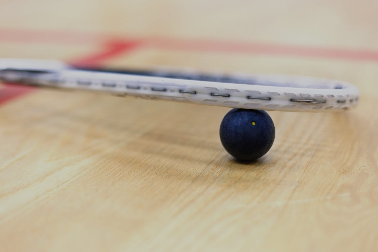 Close-up of a squash ball and racket on a squash court.