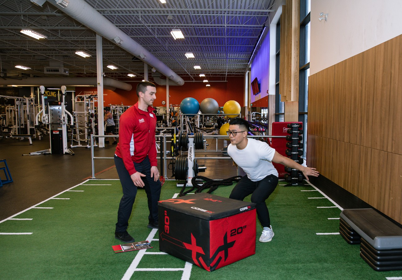 GoodLife Fitness trainer observes a client doing an exercise with medicine ball