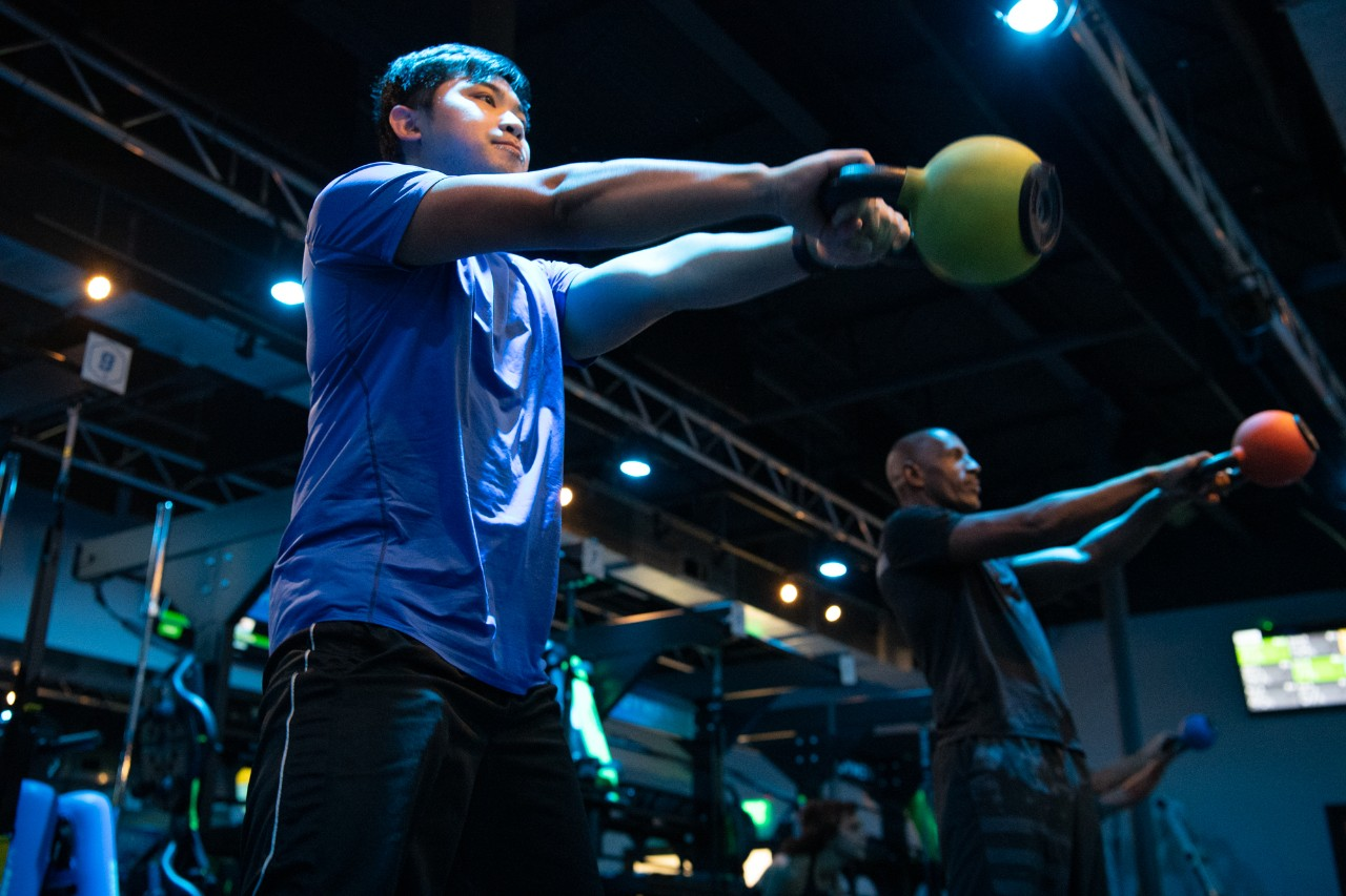 Man in blue shirt exercising with a kettle bell