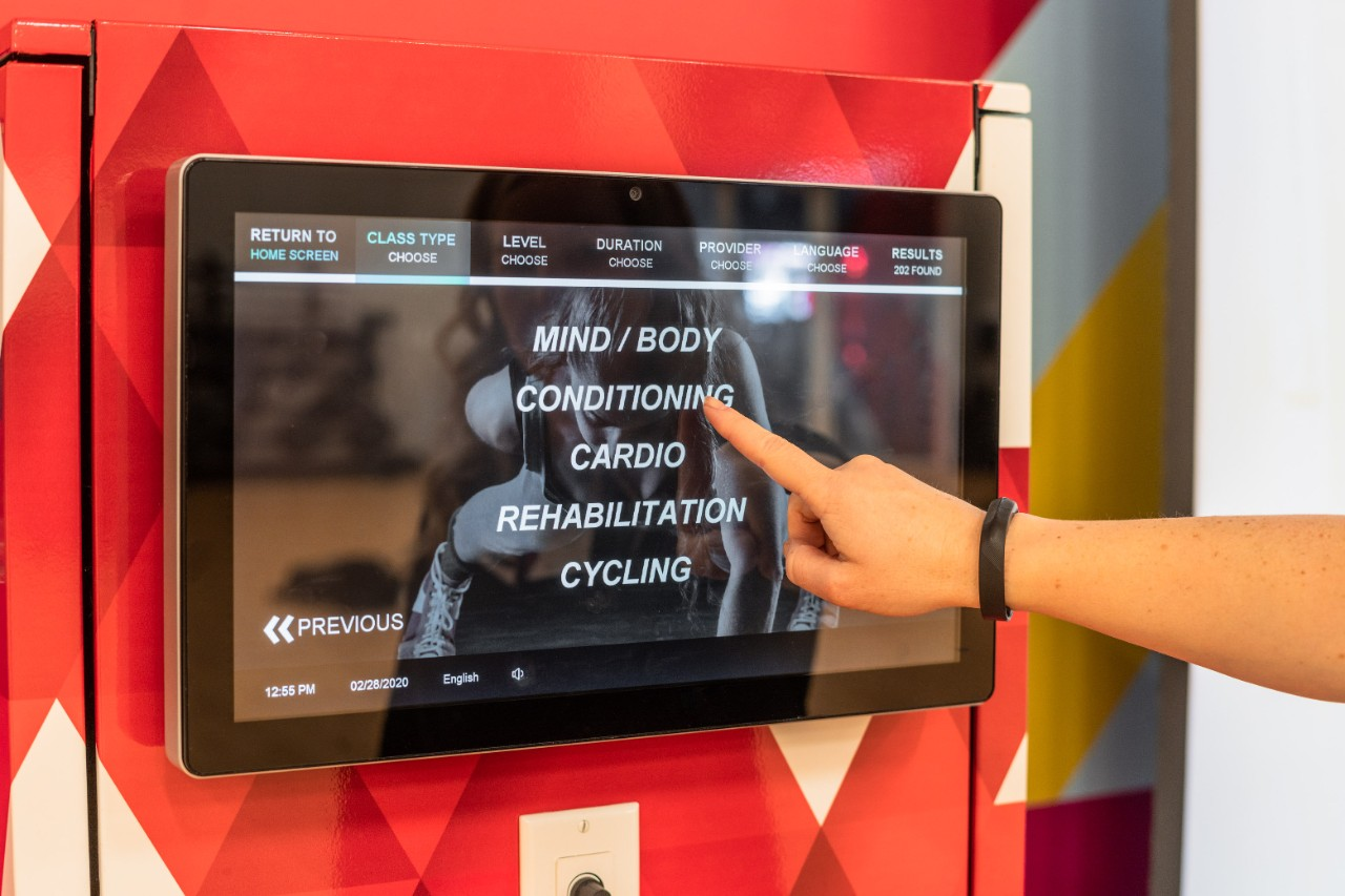 Person selecting a workout category on a touchscreen