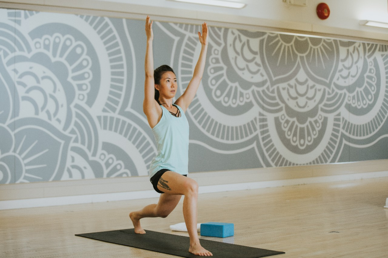 Woman standing in a crescent lunge position in a yoga studio.