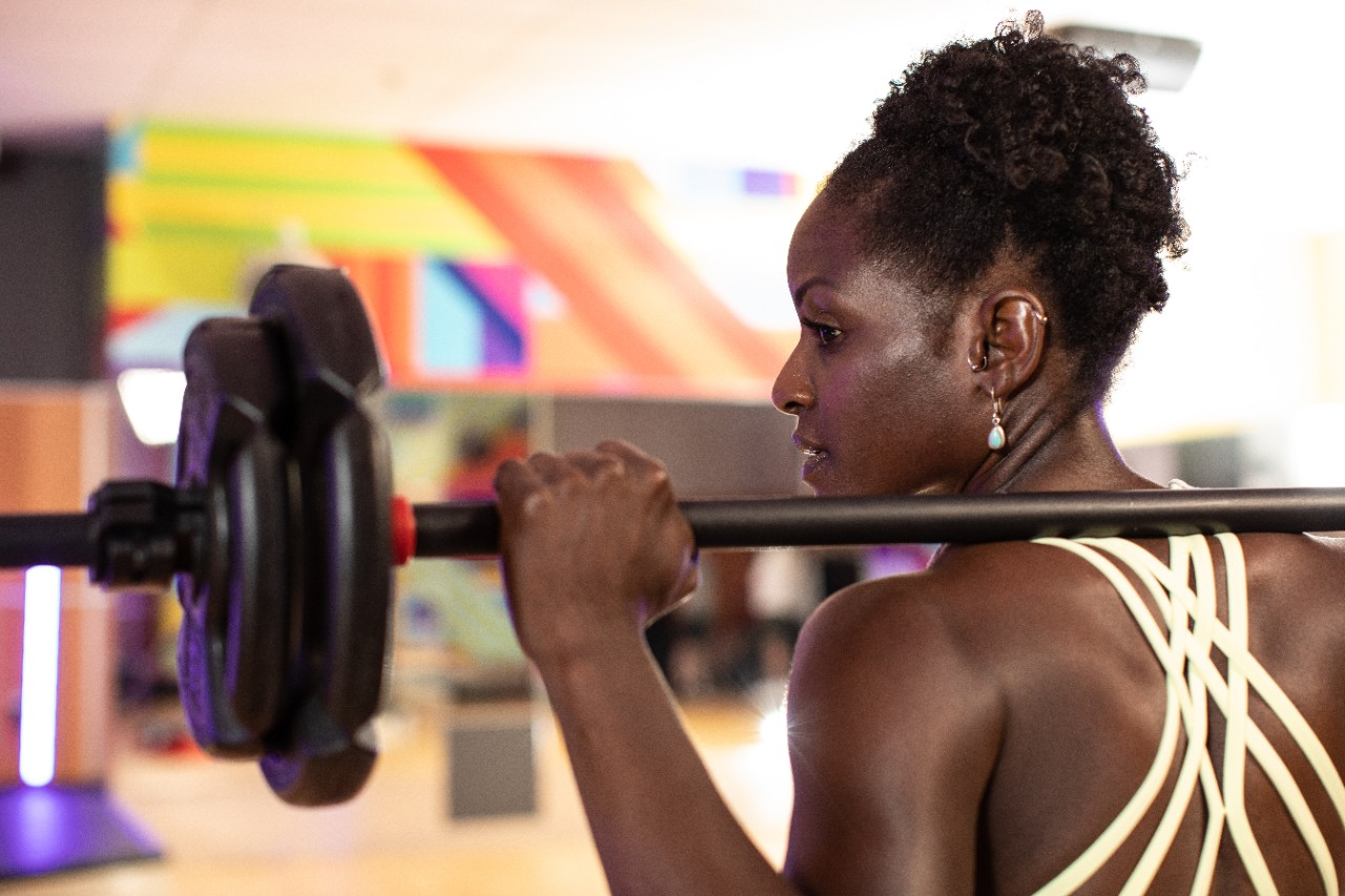 Woman holding barbell on shoulders and looking to the left