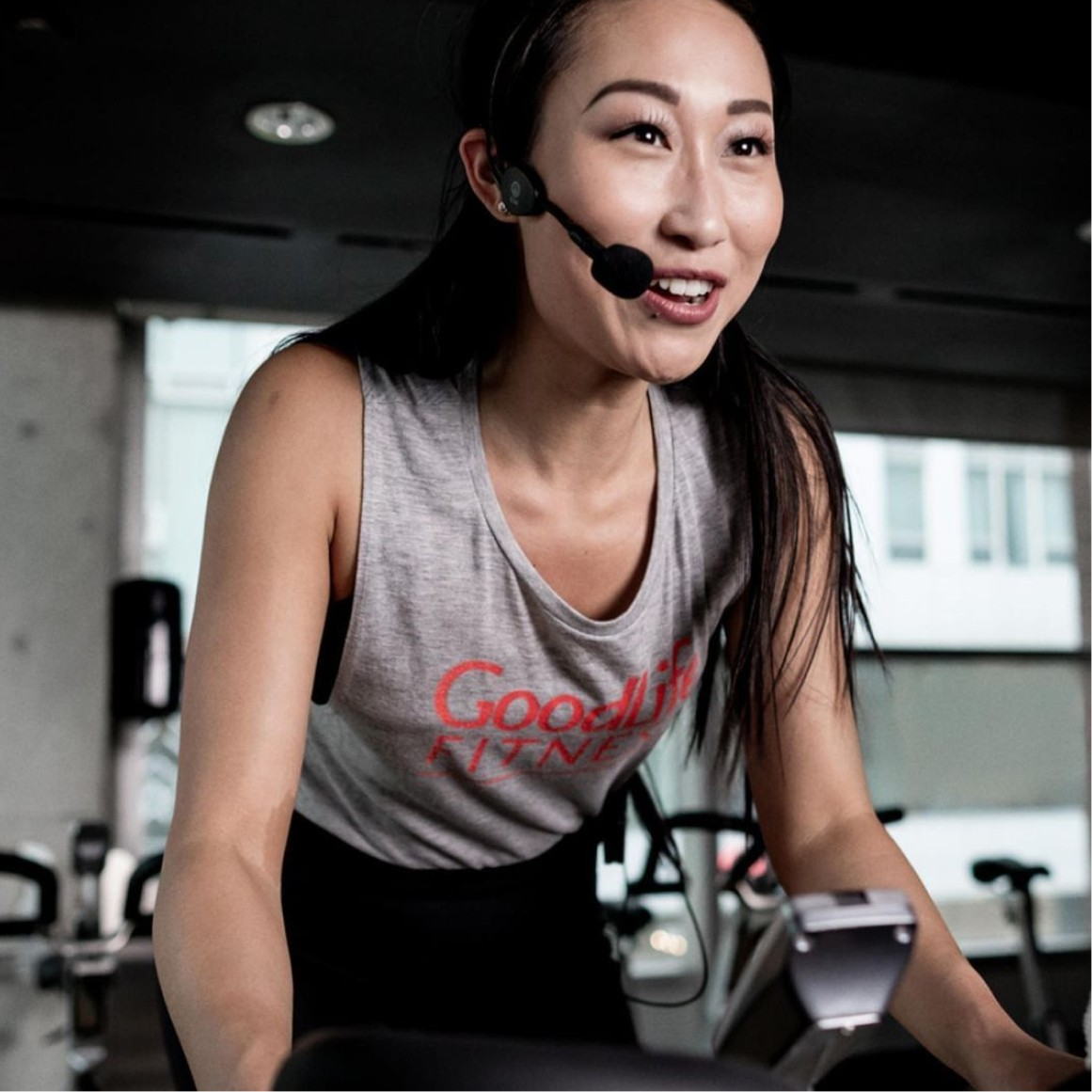 GoodLife Cycling class instructor on a stationary bike with a microphone headset