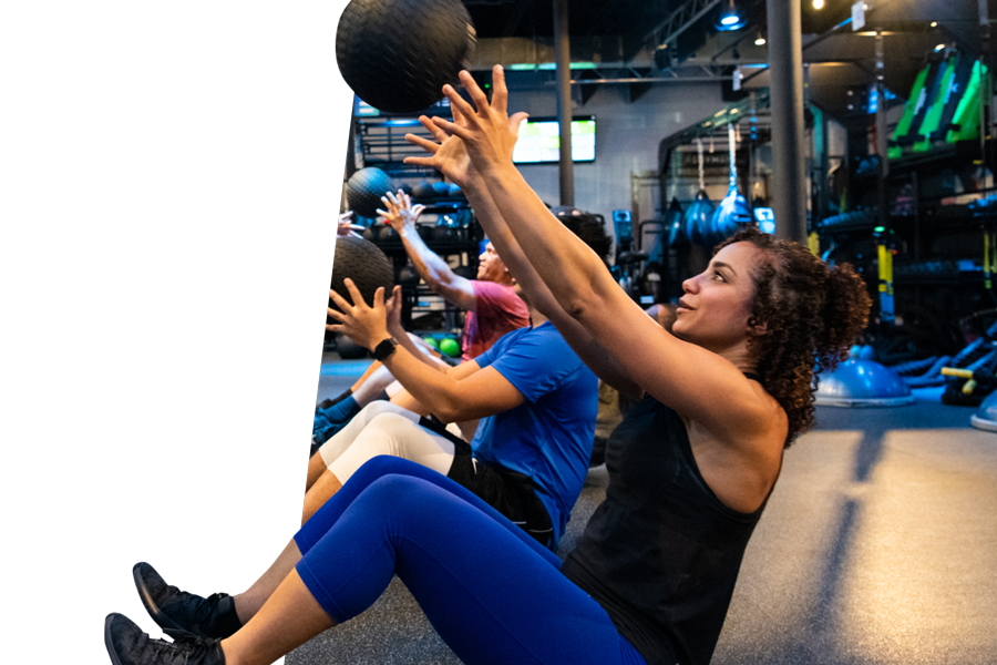 Woman sitting in boat position, catching a medicine ball.