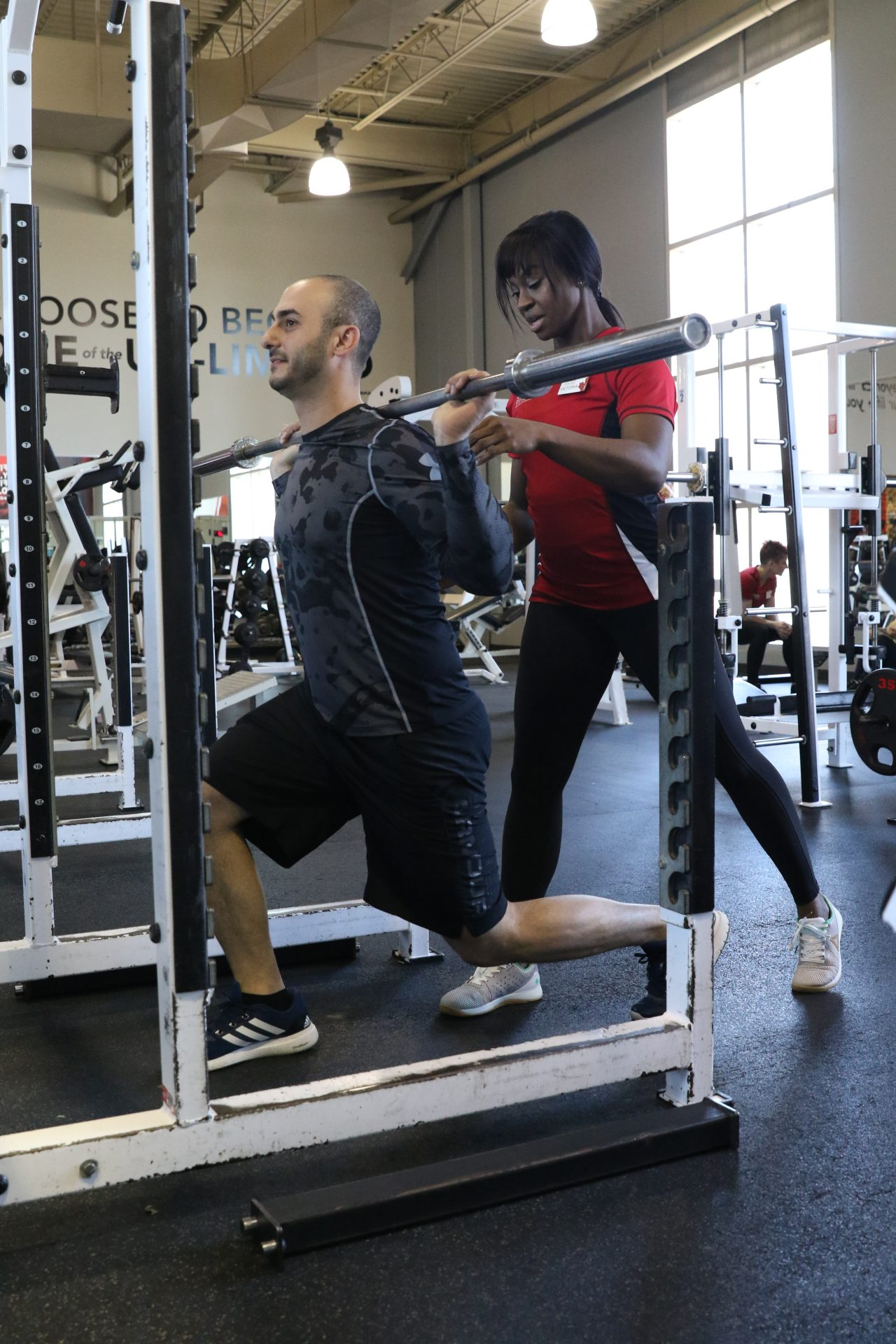 GoodLife Fitness trainer helps a client execute a bicep curl