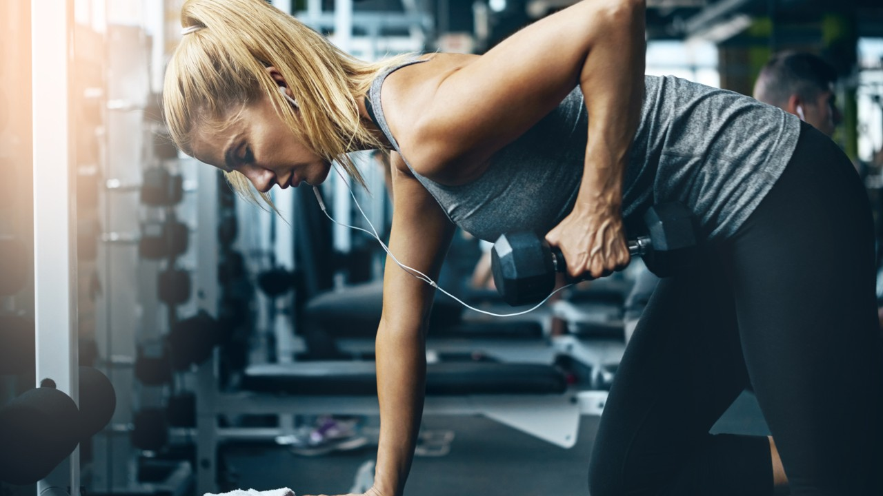 Woman wearing headphones doing single-arm row