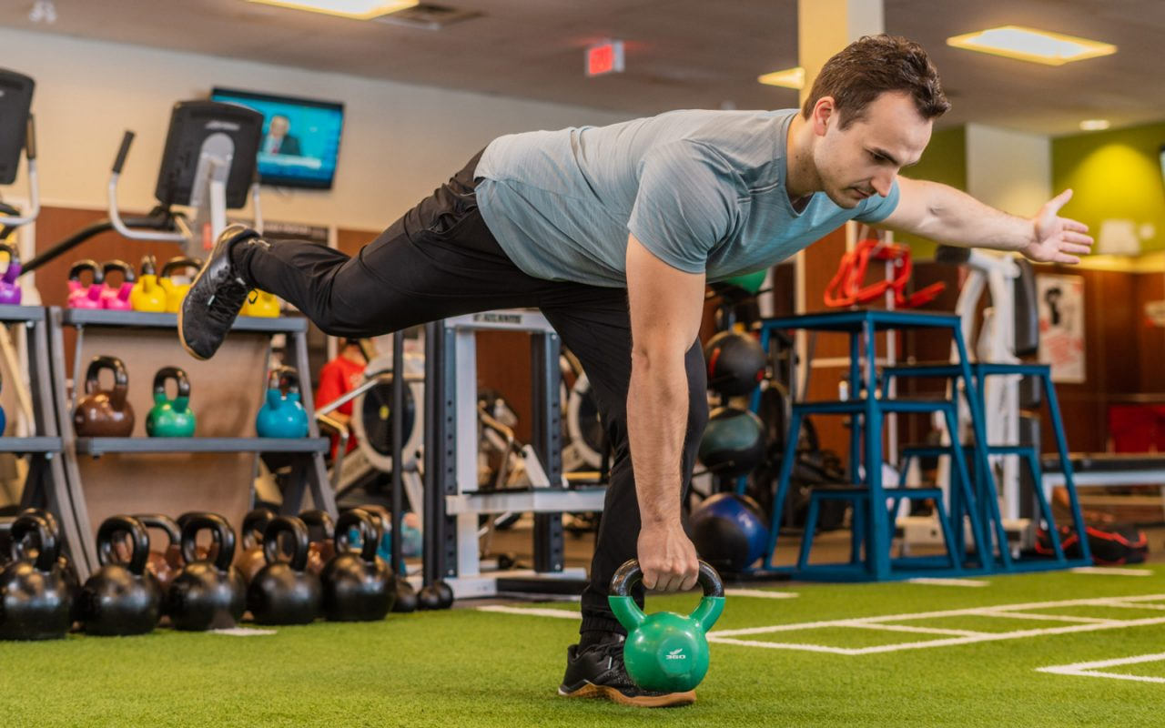 Man holding kettlebell while leaning forward and balancing on one foot on indoor turf