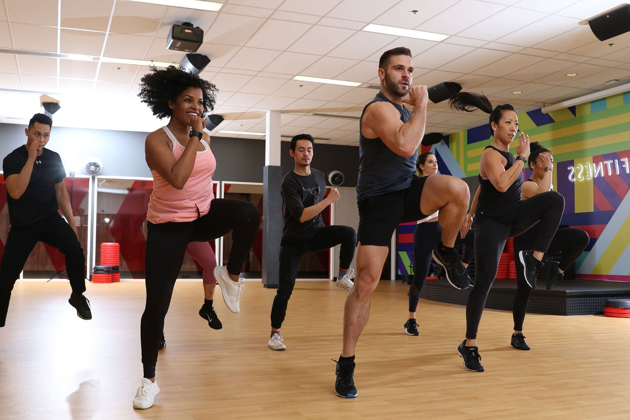 Group of seven men and women in a high-energy fitness class