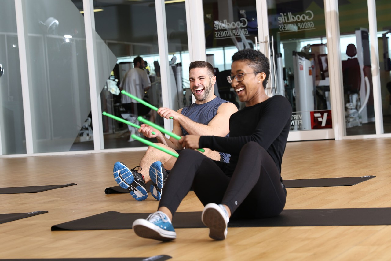 Man and woman with sticks in a GoodLife Pound class, sitting and laughing on yoga mats