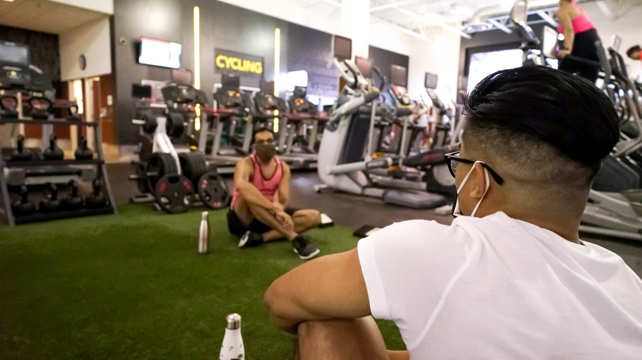 Two men sitting on turf in a GoodLife Fitness club, facing each other while socially distanced and wearing masks