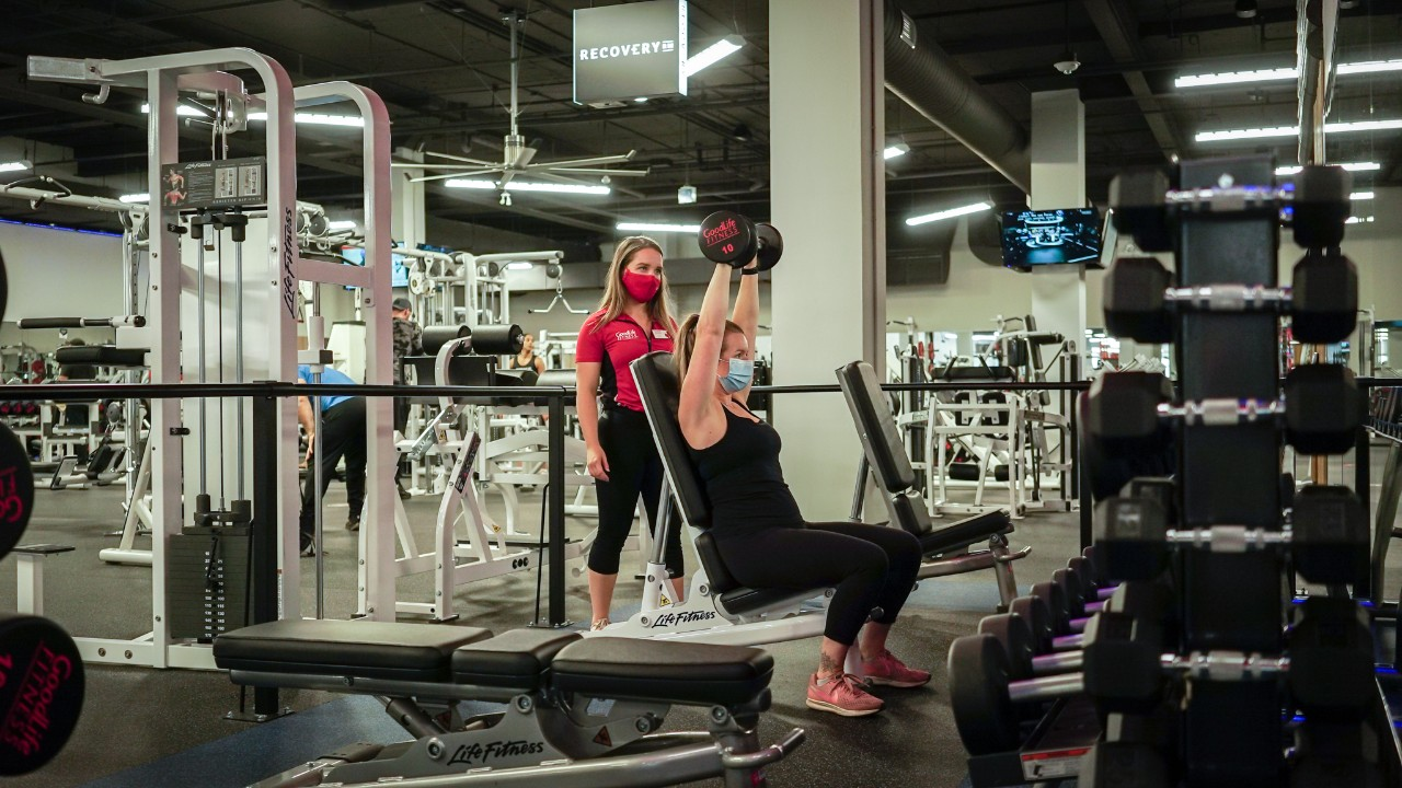 GoodLife Personal Trainer observes woman in black shirt doing shoulder press